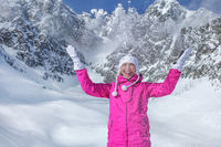 Young woman in pink winter jacket, gloves and warm hat throwing snow in the air, smiling, mountain behind her. Tatranska Lomnicka ski resort, Slovakia