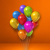 Colorful balloons bunch on orange wall background