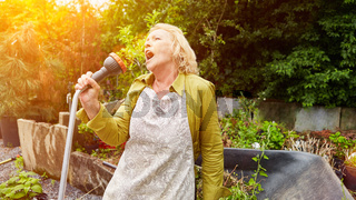 Alte Frau singt beim Blumen gießen als Lebensfreude Konzept