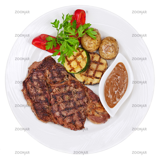 Grilled steaks, baked potatoes and vegetables on w