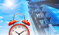 Red alarm clock on modern building and blue sky background