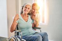 Seniorin im Rollstuhl mit Krankenpflegerin oder Tochter