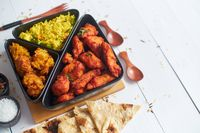 Spicy indian fried chicken served with curry vegetable rice, onion bhajia, naan bread