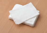 Stack of unwrapped wet wipes on wooden table