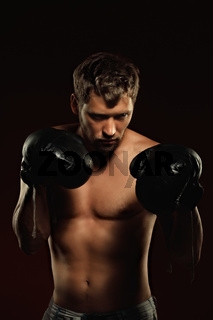 This is a dramatic portrait of a boxer in old boxing gloves on a dark background. An athletic mixed martial arts fighter