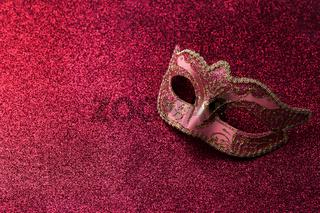 Carnival mask on red glitter background
