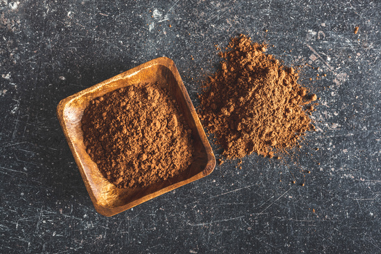 Cocoa powder in wooden bowl.