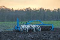 Blue plow in a field in the evening