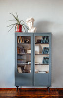 Vintage retro pastel blue bookcase standing on wooden varnished parquet floor in living room