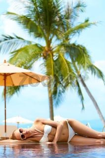 Woman sunbathing on an infinity pool