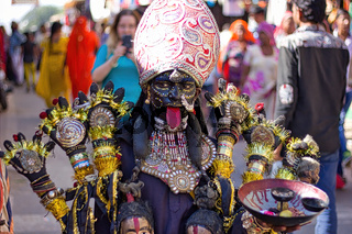 Pushkar, India - November 10, 2016: A young little girl dressed up or disguised as Indian goddess of destruction named maa Kali with crown and multiple hands as street performer during Pushkar fair