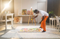 African american male painter at work painting on canvas in art studio
