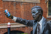 Seward Johnson's Statue of a man trying to catch a taxi home with an energy drink placed in his hand and a pair of glasses painted aruund his eyes. It is located on John Carpenter Street in London.
