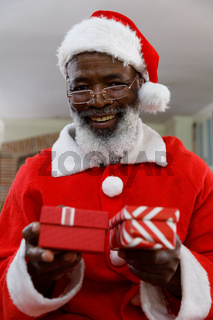 Portrait of senior african american man wearing a costume of santa claus and holding gifts