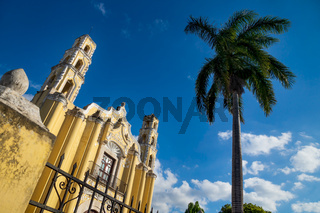 Colonial church 'San Juan Bautista' with palm tree in the historic center of Merida, Yucatan, Mexico
