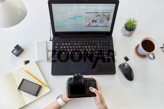 woman with camera and video editor on laptop
