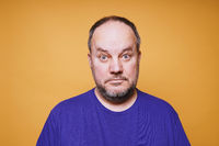 mid adult man with dumbfounded look on his face against orange color studio background