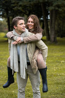 Young couple in love piggyback at a park