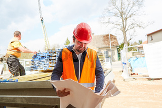Architekt oder Vorarbeiter schaut auf einen Bauplan