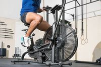 Close up of an unrecognizable man doing cardio training on stationary air bike machine with fan at the gym.