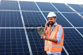 The young electrician works at a solar station using gadgets