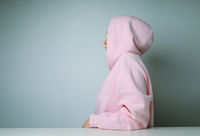 Young woman in pink hoodie posing on white background, with hood over the heads.