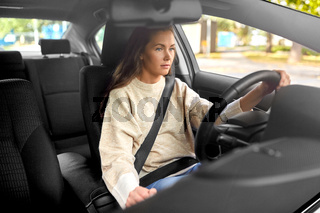 woman or female driver driving car in city