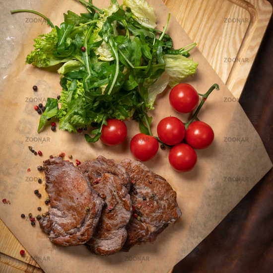 Grilled beef steak with fresh lettuce salad with arugula seeded pepper mixture and cherry tomatoes. Restaurant concept. Restaurant food. Grill concept. Square cropped