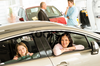 Mother and daughter trying car in dealership