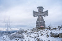 Stone war cross near Lookout tower Stepanka on the border of Krkonose and Jizera Mountains. Winter overcast day, sky with clouds, trees covered with snow.