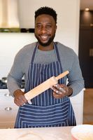 Portrait of happy african american man wearing apron, holding rolling pin in kitchen