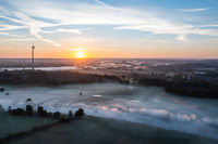 Sunrise and the first rays of sunshine over the fog-covered Ruhr meadows in Duisburg, Germany
