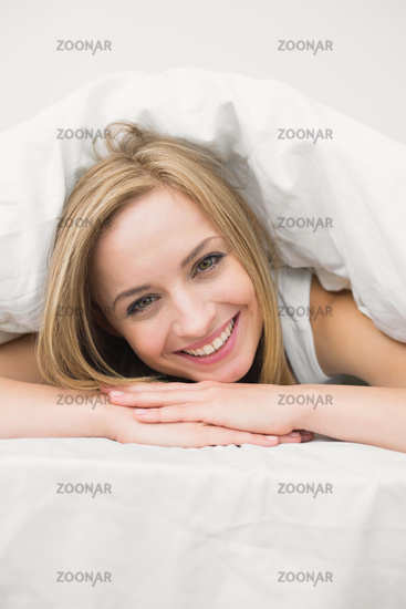 Closeup portrait of beautiful woman under sheet in bed