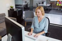 Smiling caucasian businesswoman sitting at desk in office using computer