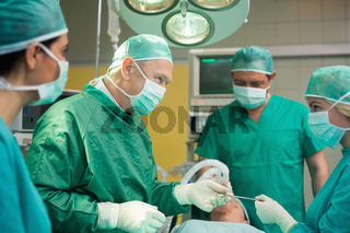 Smiling surgeon working with a team