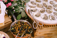 Oysters in a plate on the table with kitchen tongs and a ladle of stuffed olives.