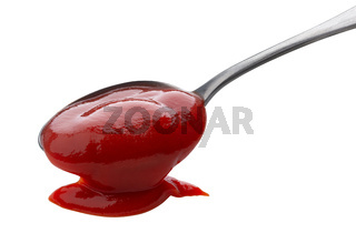 Flowing ketchup isolated on white background, tomato sauce with metal spoon