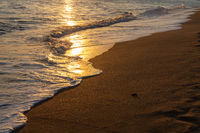 Light of golden shimmering sunset light on gentle waves on a sandy beach