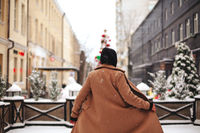 Young positive woman outside against background of winter city