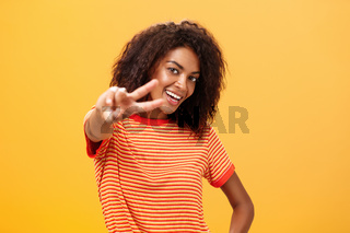 Hey peace my friend. Charming outgoing and confident carefree dark-skinned girl with afro hairstyle in trendy t-shirt pulling hand with victory gesture towards camera smiling over orange wall