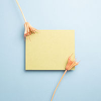 Yellow memo pad with pink dry flowers on blue background. top view, copy space