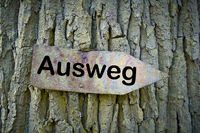 old rusty sign with the inscription way out (Ausweg) on a tree
