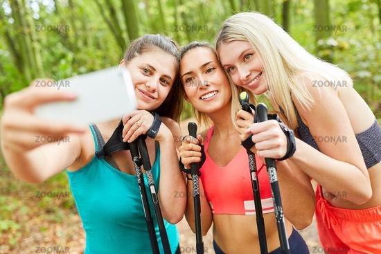 Three women take a selfie while Nordic Walking