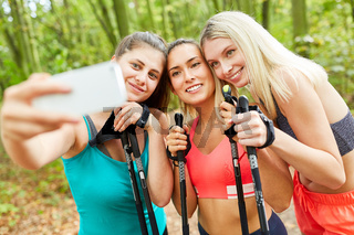 Drei Frauen machen ein Selfie beim Nordic Walking