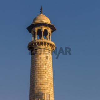 Taj Mahal's minaret lit by the warm rays of the rising sun