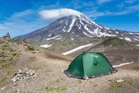 Green tourist tent Red Fox for camping and travel standing in mountain on background of volcanic landscape - cone of Koryak Volcano
