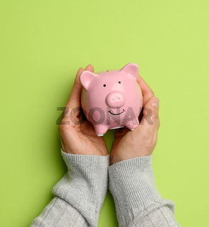hand holding pink ceramic piggy bank on a green background