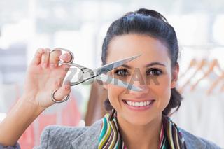 Cheerful designer holding scissors