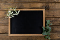 View of a black board surrounded by flowers on wood table background