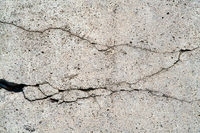 Close up of cracks in a dilapidated concrete wall on a building